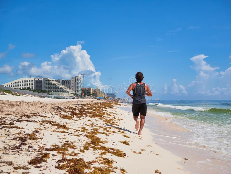 Young man jogging in tropical beach stock photos