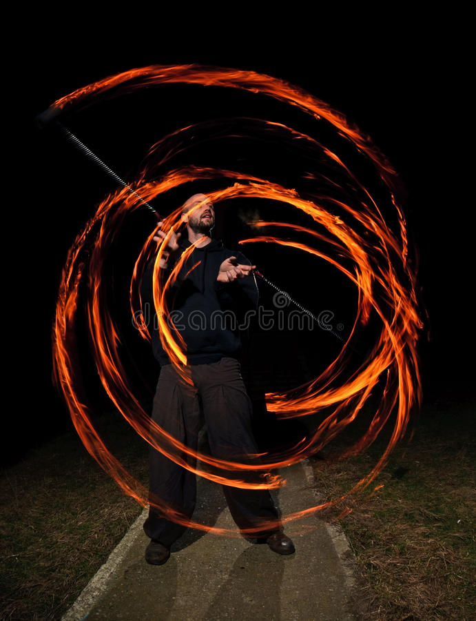 Young man juggling fire poi royalty free stock photos