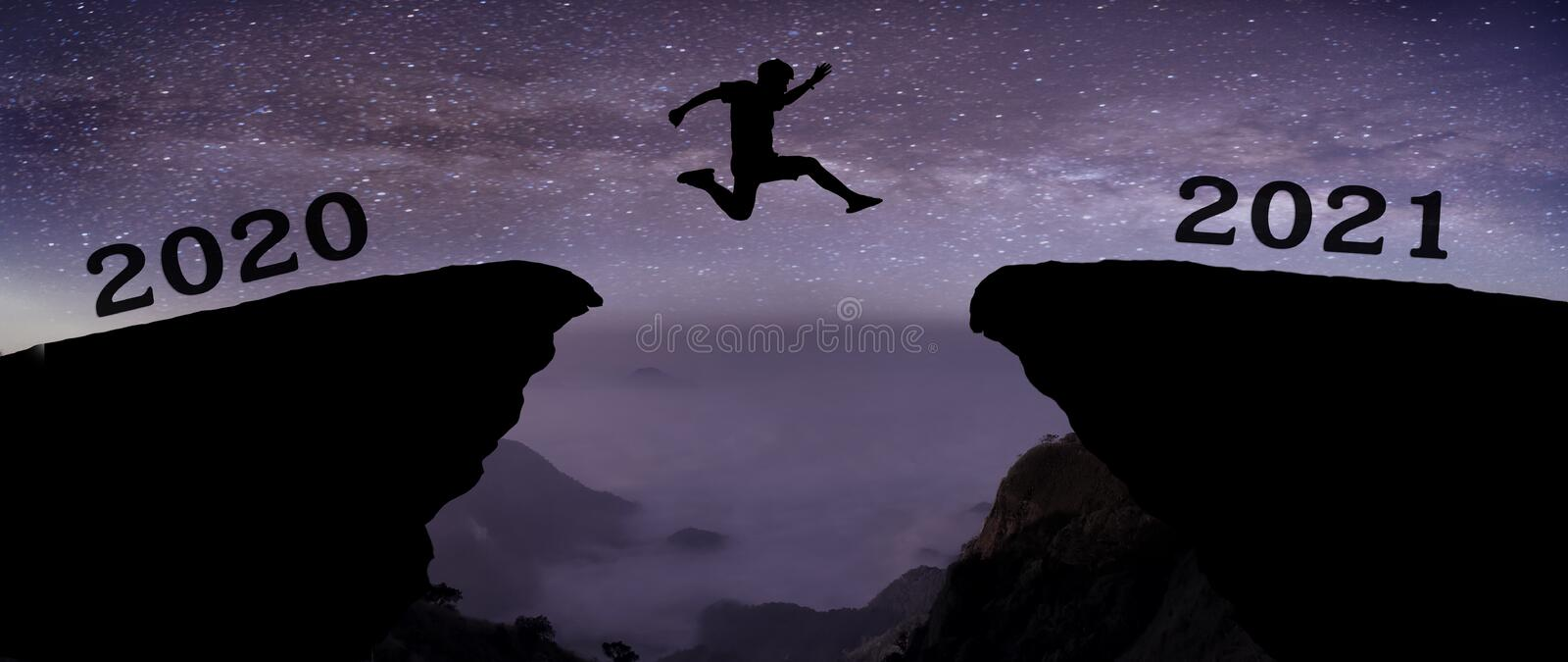 A young man jump between 2020 and 2021 years over night sky with stars and through on the gap of hill silhouette evening colorful royalty free stock photo