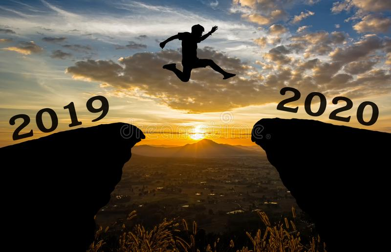 A young man jump between 2019 and 2020 years over the sun and through on the gap of hill silhouette evening colorful sky. royalty free stock photo
