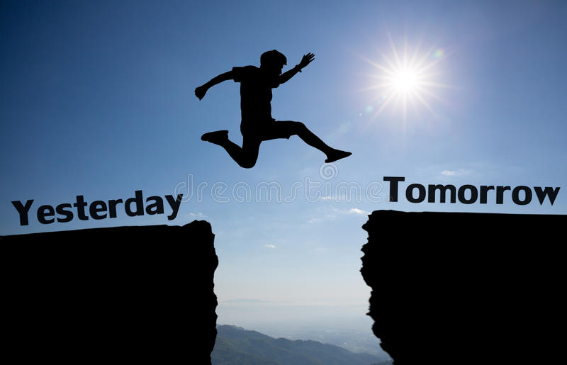 A young man jump between yesterday and tomorrow over the sun and through on the gap of hill silhouette evening colorful sky. Man is representative of success royalty free stock photo
