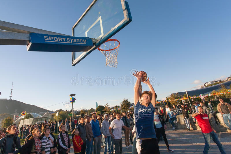 Young man jumping with ball on basketball playground during popular city festival stock photos