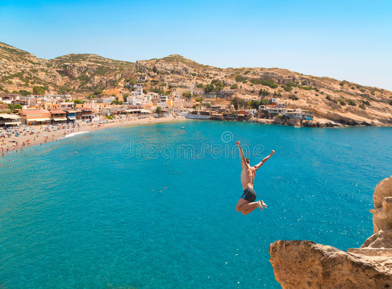 Young man jumping from the cliff in the sea. royalty free stock image