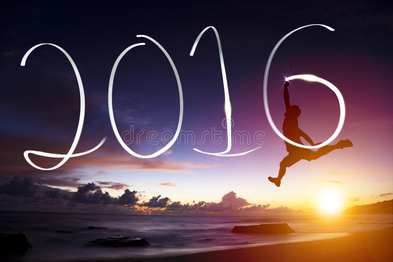Young man jumping and drawing 2016 on beach stock photography