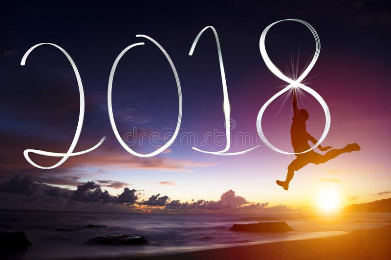 Young man jumping and drawing 2018. Happy new year concept.young man jumping and drawing 2018 royalty free stock images