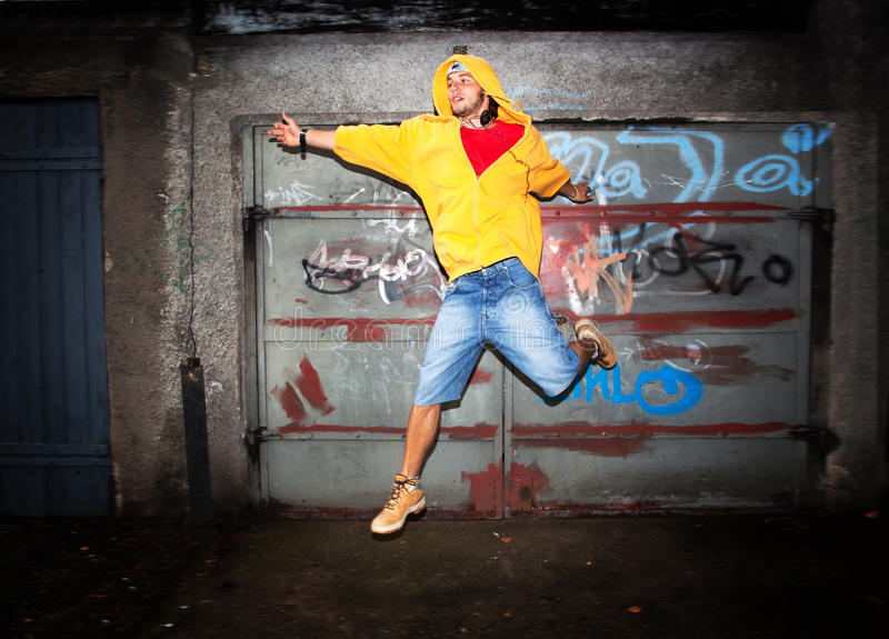 Young man jumping, grunge. Young man jumping / dancing on grunge graffiti wall background stock photo