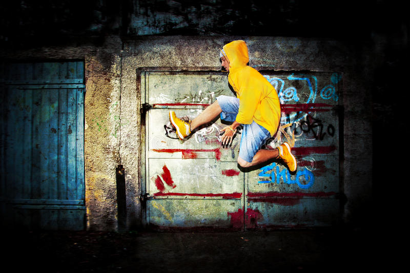 Young man jumping, grunge. Young man jumping / dancing on grunge graffiti wall background stock images