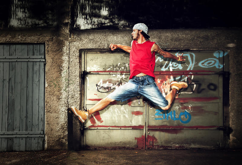 Young man jumping, grunge. Young man jumping / dancing on grunge graffiti wall background royalty free stock photo