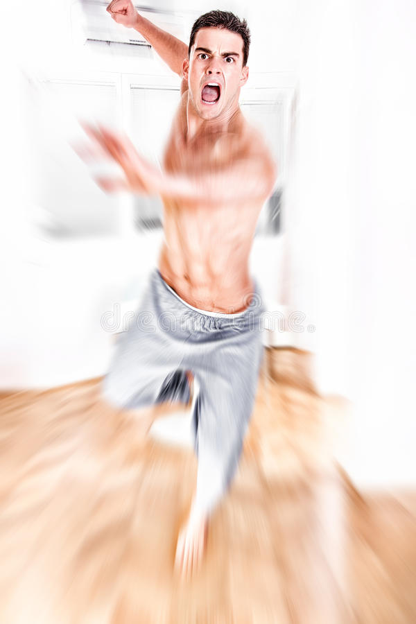 Young man jumping with kicking and clenched fists stock images