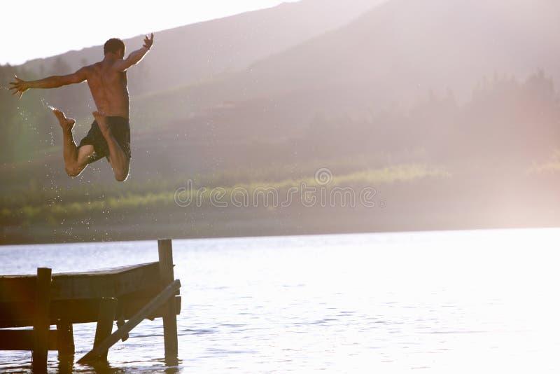 Young man jumping into lake stock photos