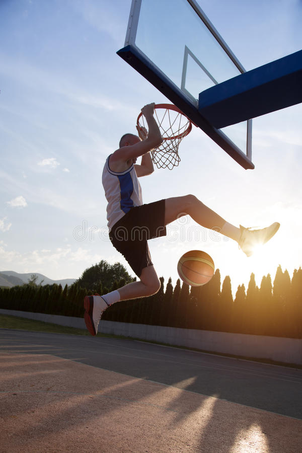 Young man jumping and making a fantastic slam dunk playing stree. Tball, basketball. Urban authentic stock photos