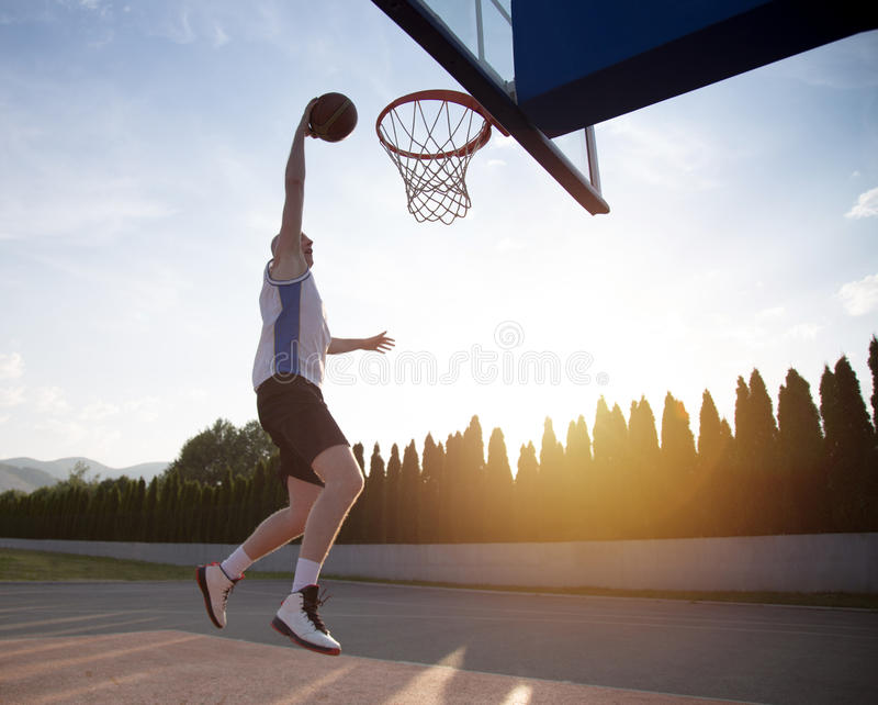 Young man jumping and making a fantastic slam dunk playing stree. Tball, basketball. Urban authentic royalty free stock photos
