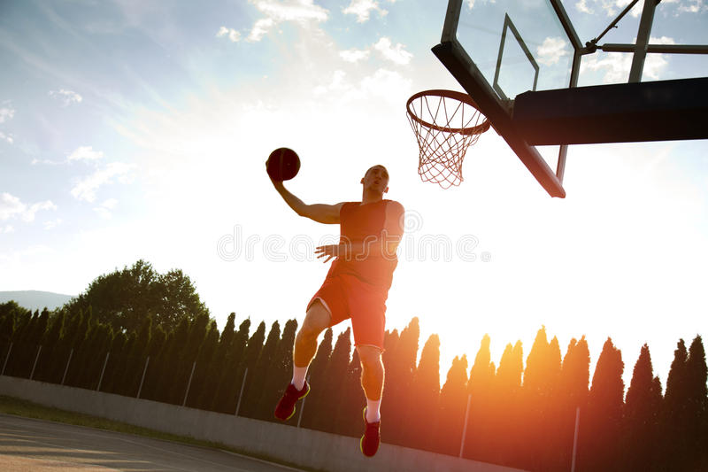 Young man jumping and making a fantastic slam dunk playing stree. Tball, basketball. Urban authentic royalty free stock photo