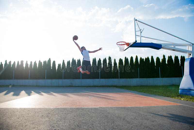 Young man jumping and making a fantastic slam dunk playing stree. Tball, basketball. Urban authentic stock photo