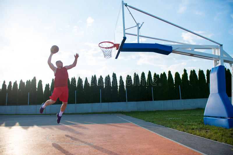 Young man jumping and making a fantastic slam dunk playing stree. Tball, basketball. Urban authentic stock images