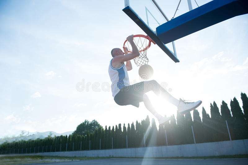 Young man jumping and making a fantastic slam dunk playing stree stock photography