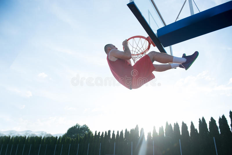 Young man jumping and making a fantastic slam dunk playing stree royalty free stock images