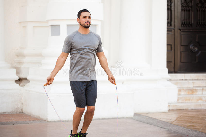 Young man jumping a rope outdoors stock image