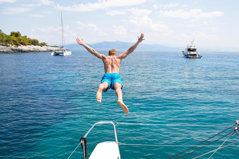Young man jumping from a sailing boat. stock images