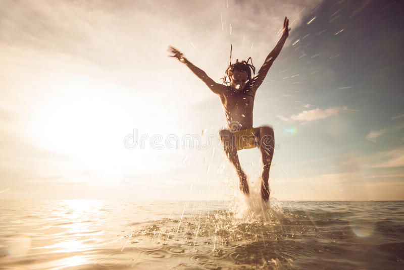 Young man jumping in the sea stock photos