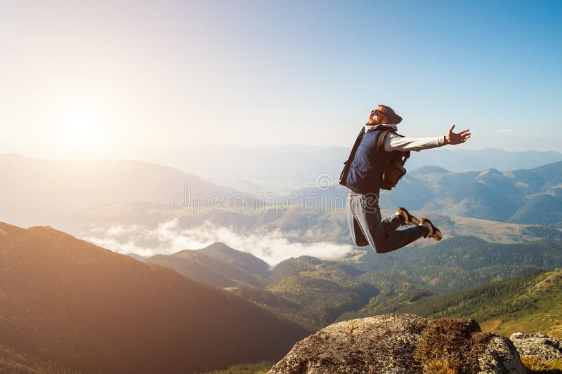 Young man jumping on top of a mountain against the sky stock images