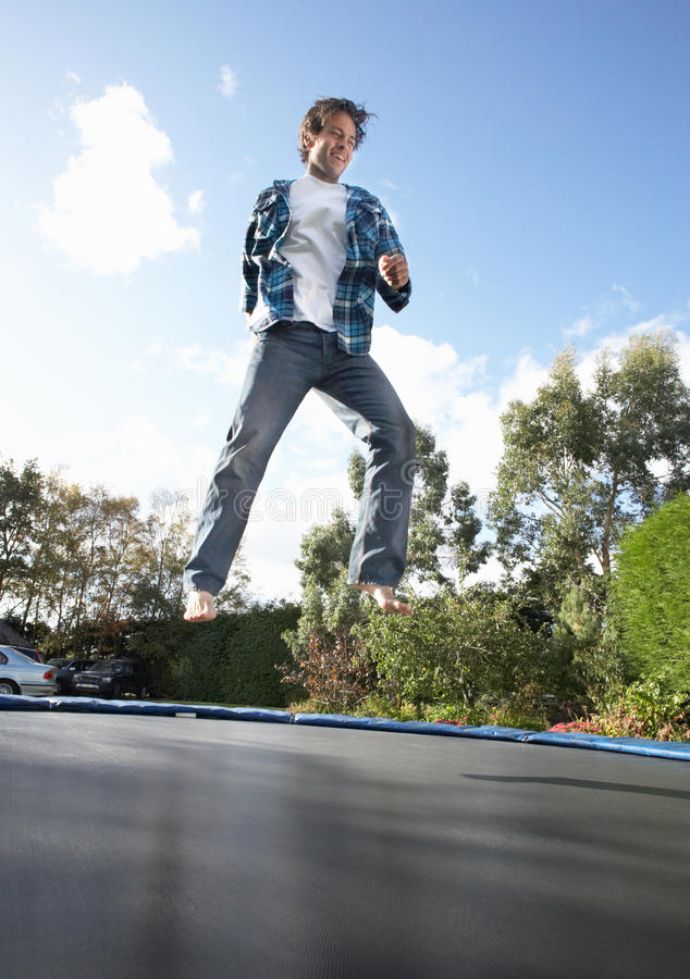 Young Man Jumping On Trampoline Caught In Mid Air royalty free stock photography