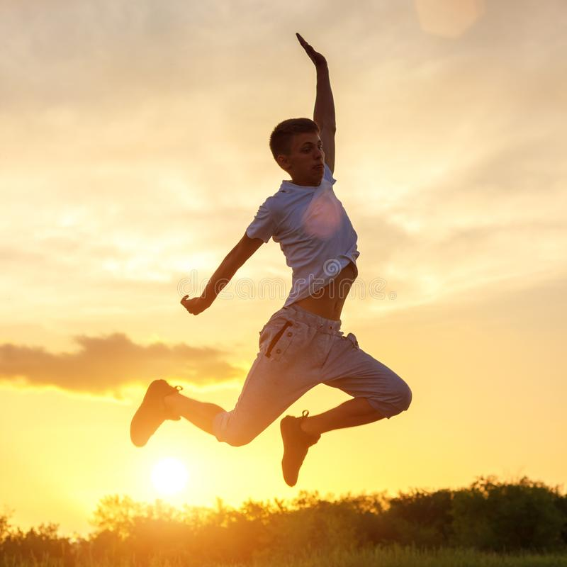Young man jumping up against the sunset sky royalty free stock image