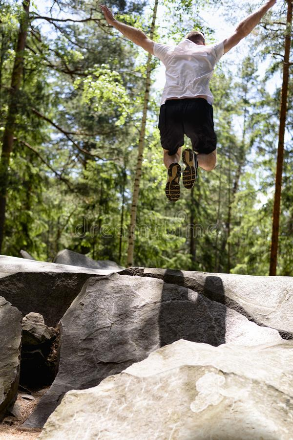 Young man jumps on a rock in a coniferous forest. Active extreme tourism stock photo