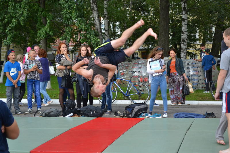Young man jumps with rotation. Vologda, Russia - August 27, 2016: Festival `Breathing of streets` boys to show their audience skills. The young man makes a stock photo