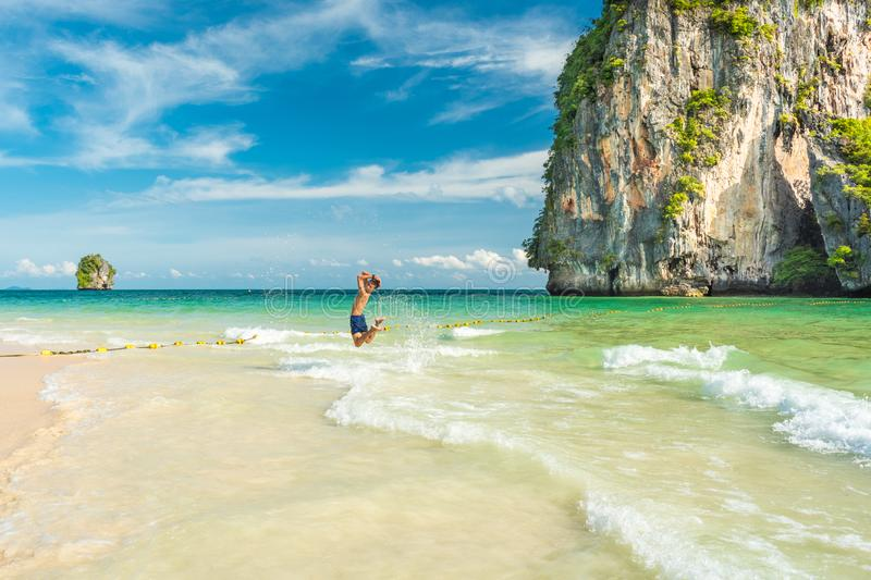 Young man jumps in the shallow sea waters with a large limestone cliff covered with tropical vegetation. In the background. Phra Nang Phranang Beach on Railay royalty free stock photo