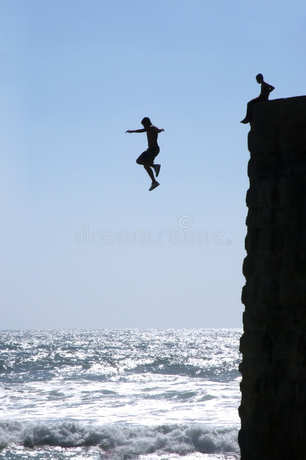 The young man jumps in water. stock photo