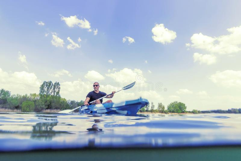 Young Man Kayak sul lago, Kayaking Underwater View, Split Shot fotografia stock