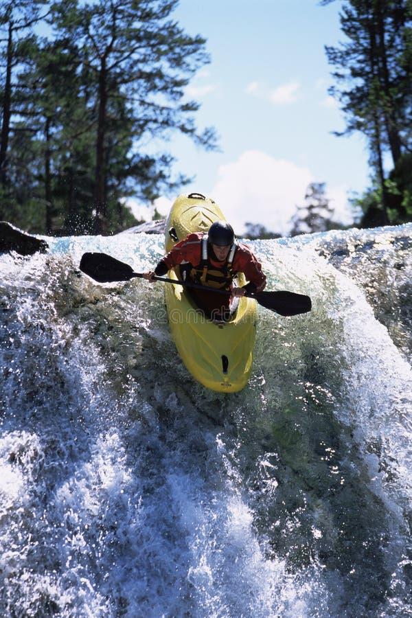 Young man kayaking down waterfall stock image