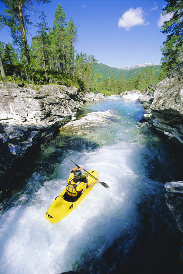 Young man kayaking in river stock photography