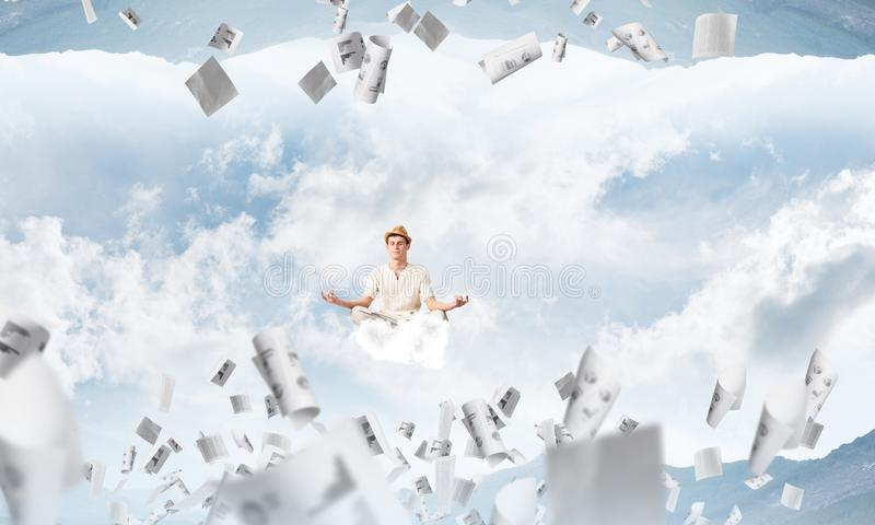 Young man keeping mind conscious. Young man keeping eyes closed and looking concentrated while meditating on cloud among flying papers and between two nature stock illustration