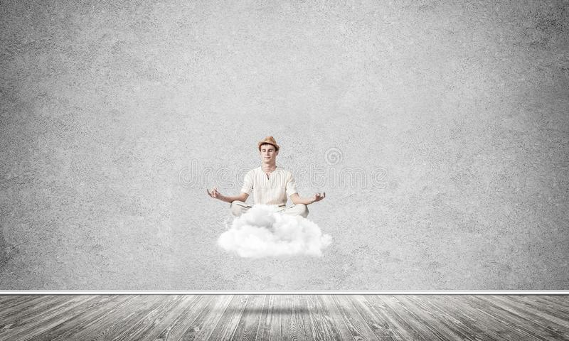 Young man keeping mind conscious. Young man keeping eyes closed and looking concentrated while meditating on cloud in the air with gray concrete wall on royalty free illustration