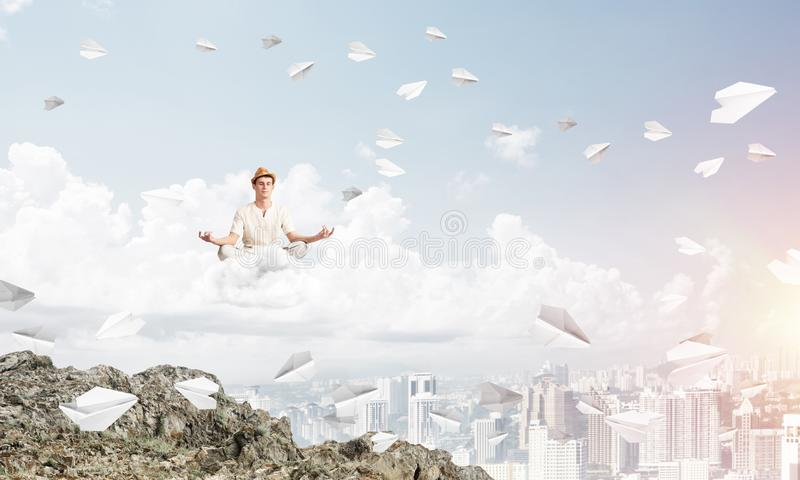 Young man keeping mind conscious. Young man keeping eyes closed and looking concentrated while meditating on cloud among flying paper planes with city view on vector illustration