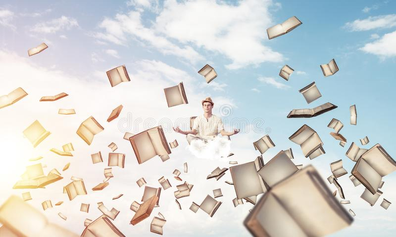 Young man keeping mind conscious. Man in white clothing keeping eyes closed and looking concentrated while meditating among flying books in the air with cloudy royalty free illustration