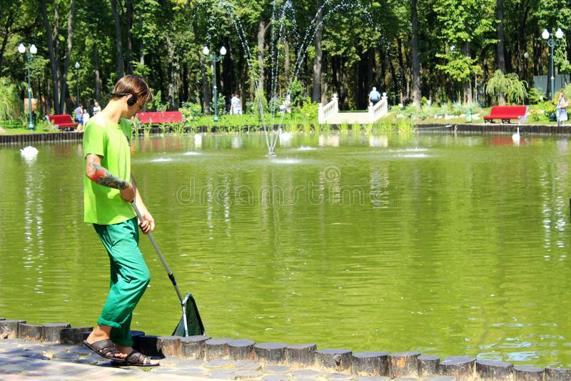 Young man keeps cleanliness in the city pond. In Kharkiv city stock photo