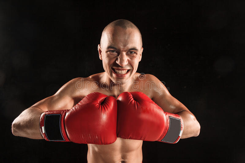 The young man kickboxing on black with screaming face. The young male athlete kickboxing on a black background with screaming face. concept fury in the fight stock photos