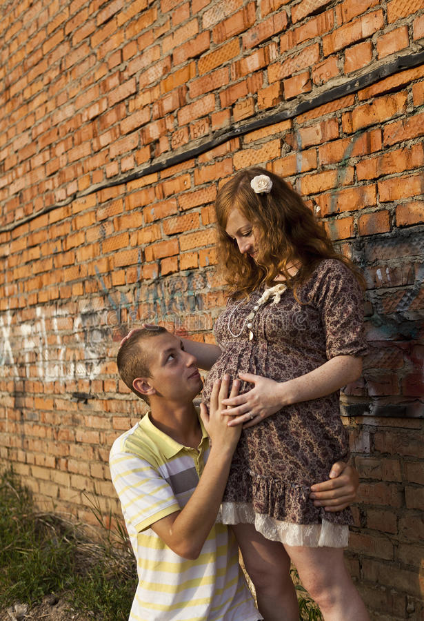 Young man kisses his pregnant wife