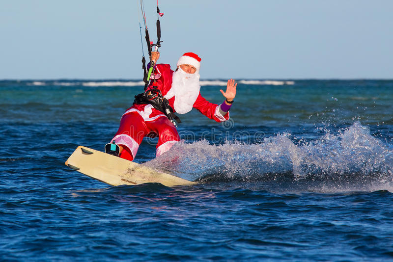 Young man on the kite in the costume of Santa Claus. Christmas a. Nd New year on a tropical island. Extreme Sport Kitesurfing royalty free stock photos
