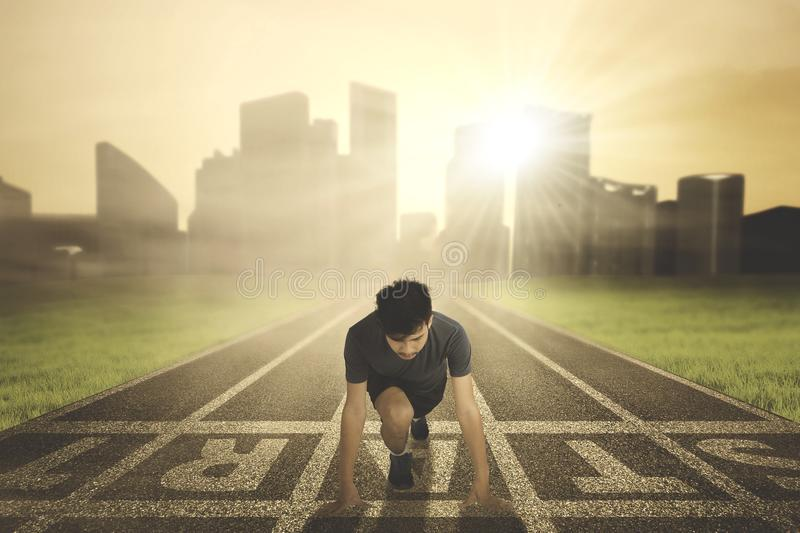 Young man kneeling on the start line. Picture of a young man ready to run while kneeling on the start line. Shot at sunrise time royalty free stock image
