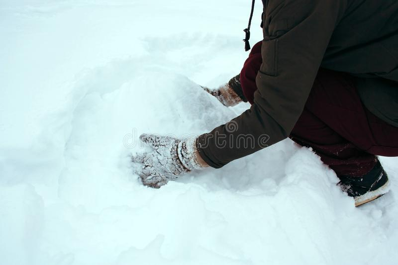 man in knitted gloves sculpts a snowman in a snow-covered park royalty free stock images