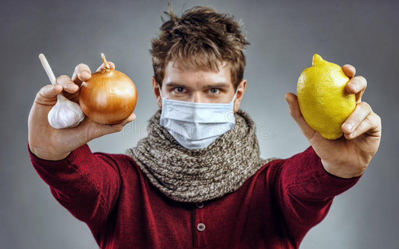 The young man knows what foods from a chill: garlic, onion, lemon. Chill prevention. The young man knows what foods from a chill: garlic, onion, lemon. Health royalty free stock photos