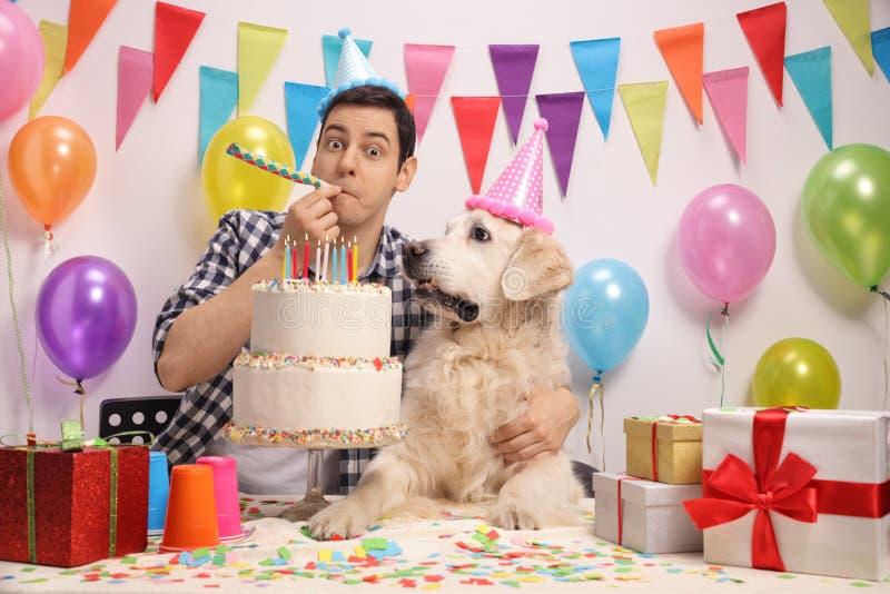 Young man with a labrador retriever celebrating a birthday royalty free stock photos