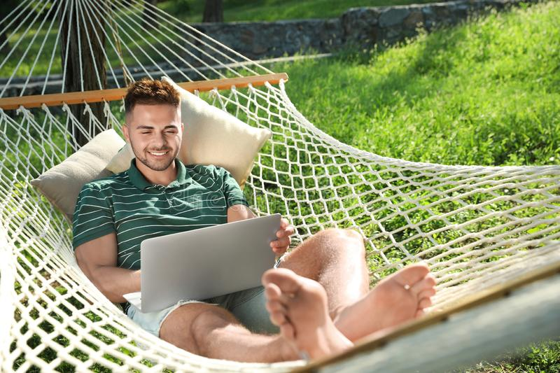 Young man with laptop resting in comfortable hammock at garden royalty free stock image