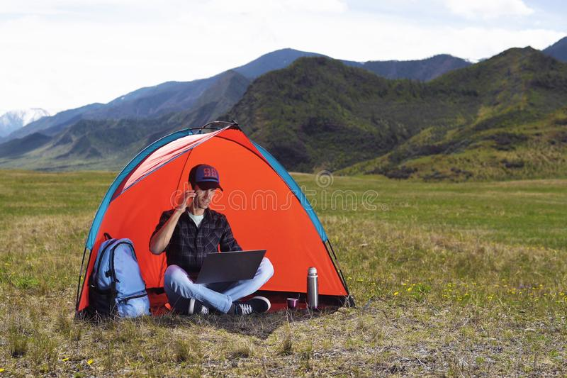 Young man with a laptop sitting in a tent against the mountains and hills of Altai and talking on a cell phone. The royalty free stock photography