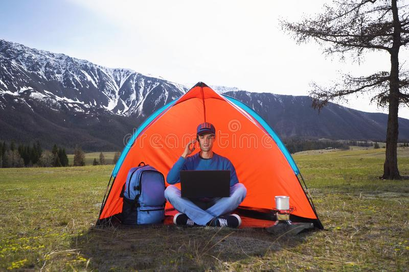 Young man with a laptop sitting in a tent against the mountains and hills of Altai and talking on a cell phone. The royalty free stock photos