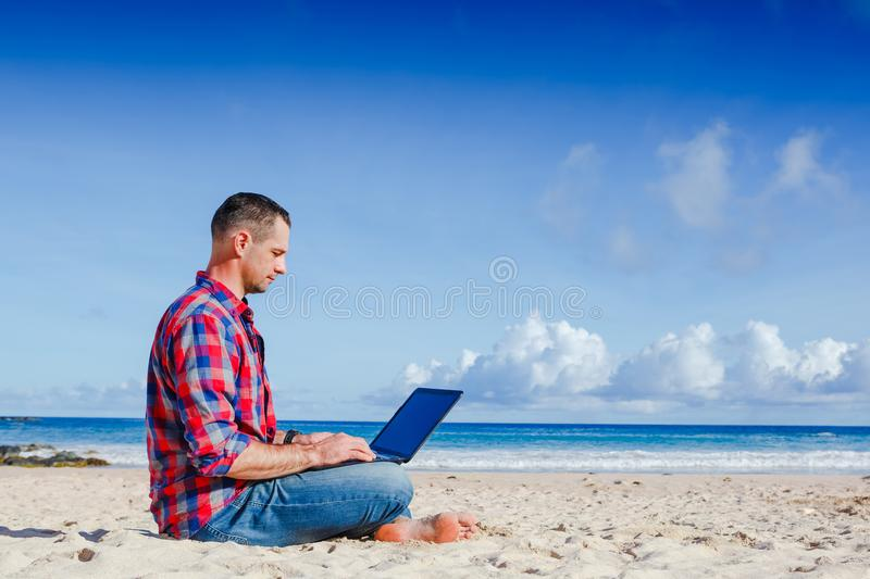 Young man with laptop working outdoor royalty free stock image